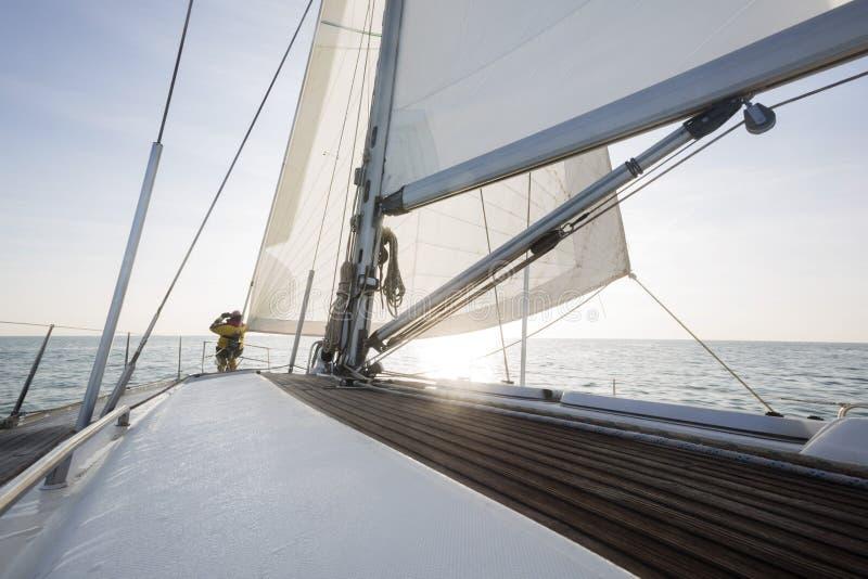 Mann, der auf Front Of Sail Boat Deck im Meer steht stockbilder