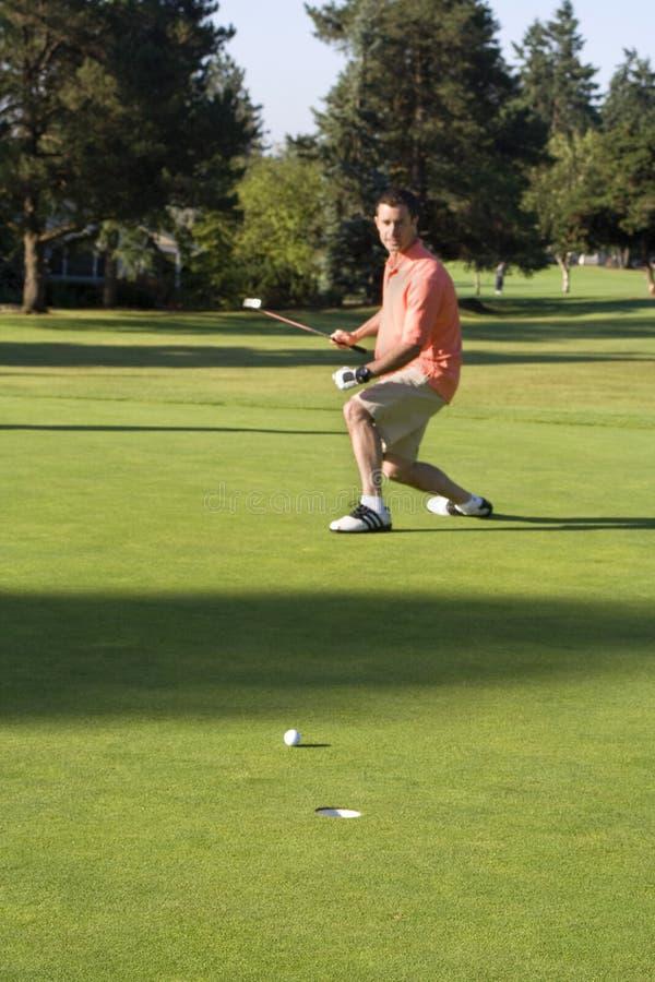Mann, der auf Golfplatz sich setzt lizenzfreie stockfotografie