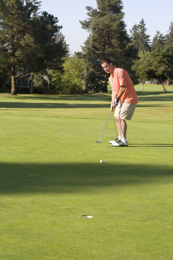 Mann, der auf Golfplatz sich setzt stockfotos