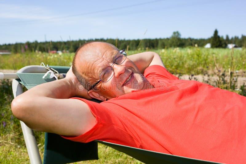 Mann, der auf Hängematte sich entspannt lizenzfreie stockfotos