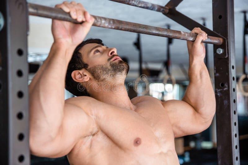 Mann, der auf horizontale Stange an der Turnhalle festzieht stockbild