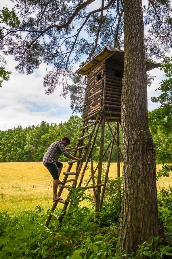 Mann, der auf Jägerhütte klettert stockfoto
