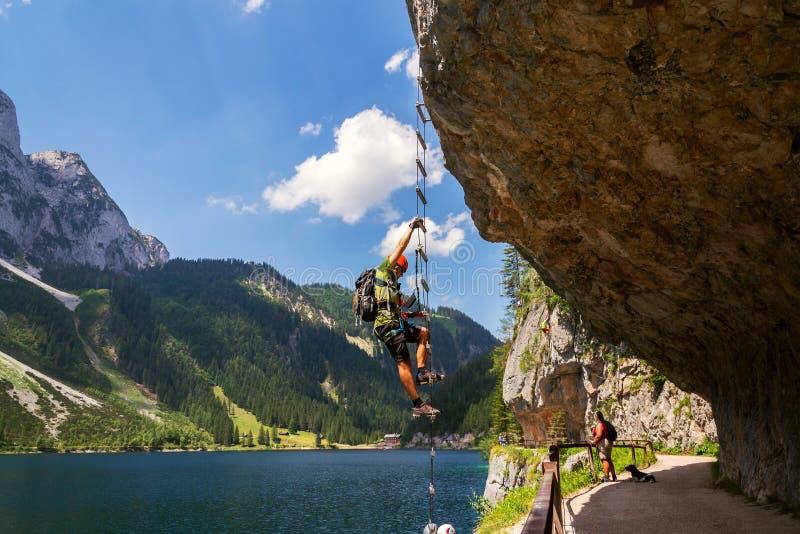 Mann, der auf Laserer-alpin über ferrata über Vorderer Gosausee See mit groberem Donnerkogel klettert stockbilder