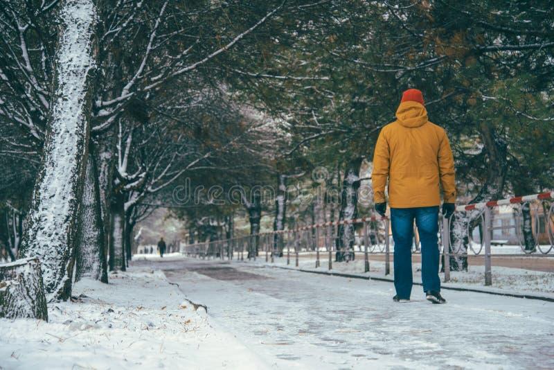 Mann, der auf Schneestraße geht lizenzfreie stockbilder