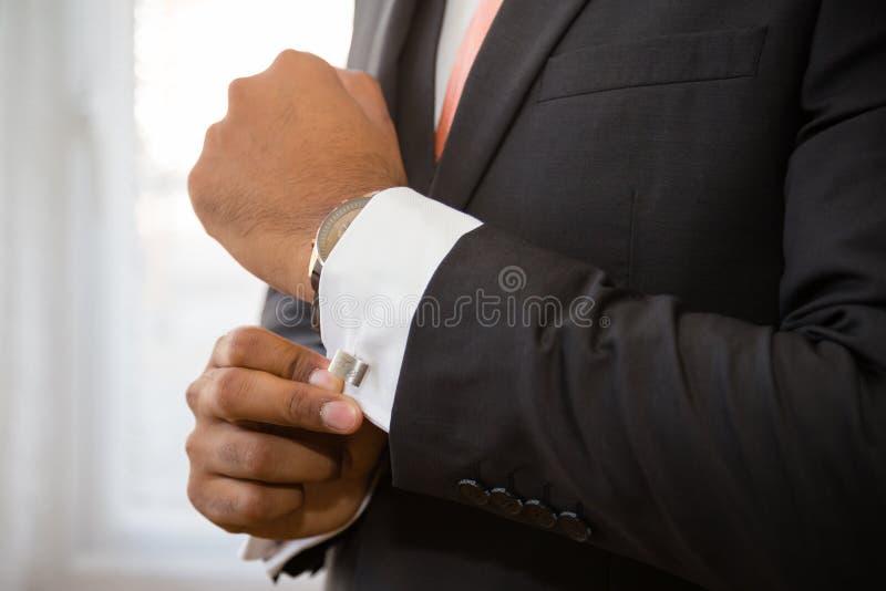 Mann, der auf seine cufflicnks sich setzt stockfotos