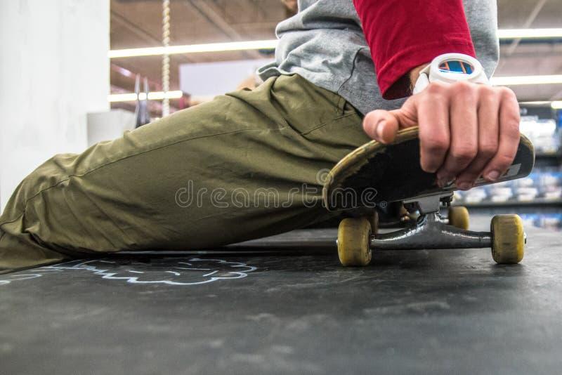 Mann, der auf Skateboard sitzt lizenzfreies stockbild