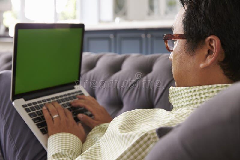 Mann, der auf Sofa At Home Using Green-Schirm-Laptop sich entspannt lizenzfreies stockbild