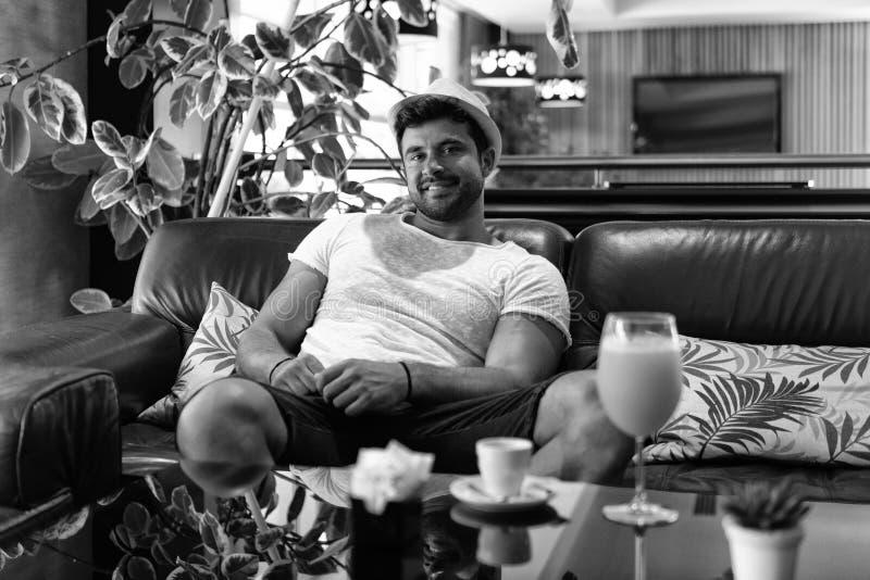 Mann, der auf Sofa im Hotel-Lobby Bar sich entspannt stockbild