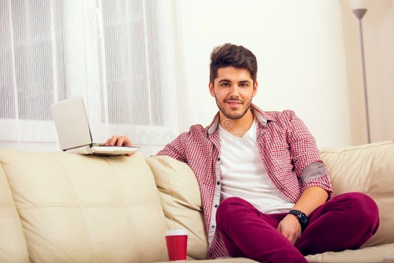 Mann, der auf Sofa mit Laptop sitzt lizenzfreie stockfotos