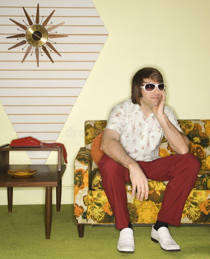 Mann, der auf Sofa sitzt. stockfotografie