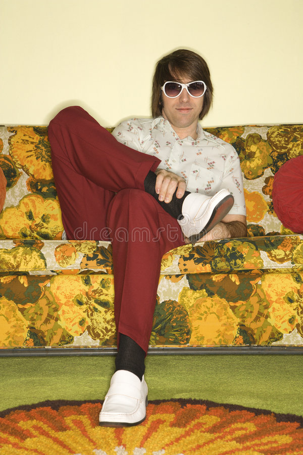Mann, der auf Sofa sitzt. stockbilder