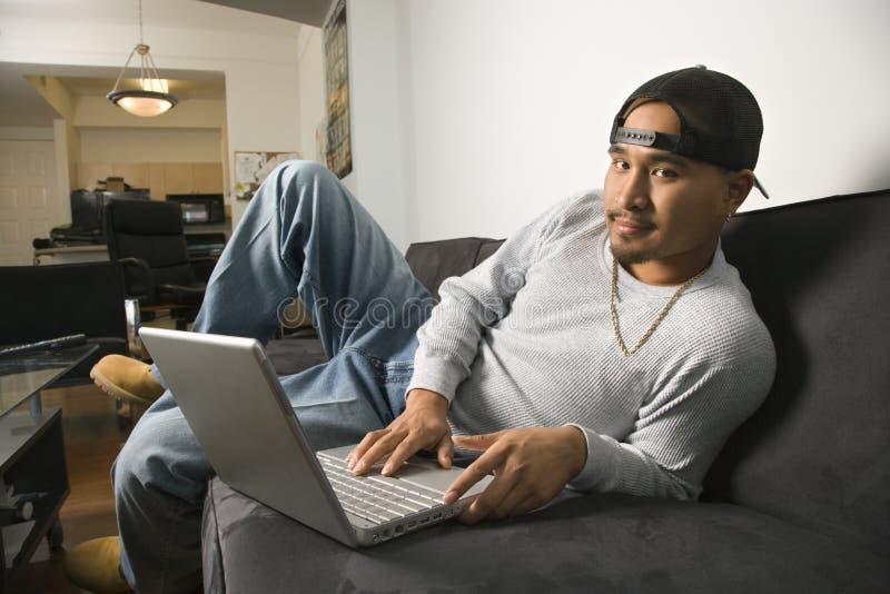 Mann, der auf Sofa unter Verwendung des Laptops sitzt. lizenzfreies stockbild