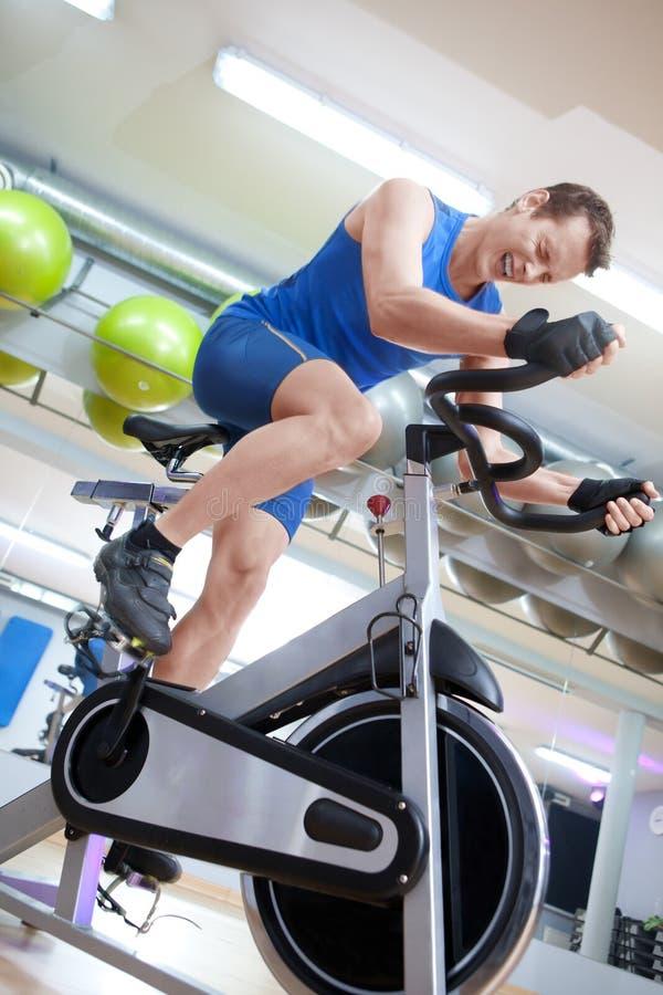 Mann, der auf spinnendes Fahrrad mit großer Anstrengung einen Kreislauf durchmacht stockbilder
