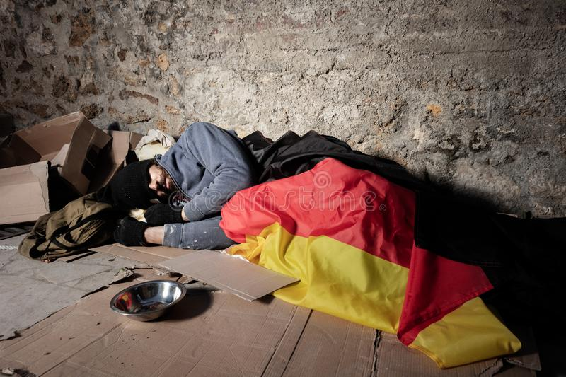 Mann, der auf der Straße unter deutscher Flagge schläft stockfoto