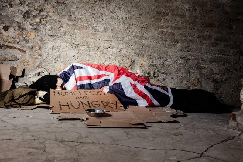 Mann, der auf Straße unter Großbritannien-Flagge schläft lizenzfreies stockbild