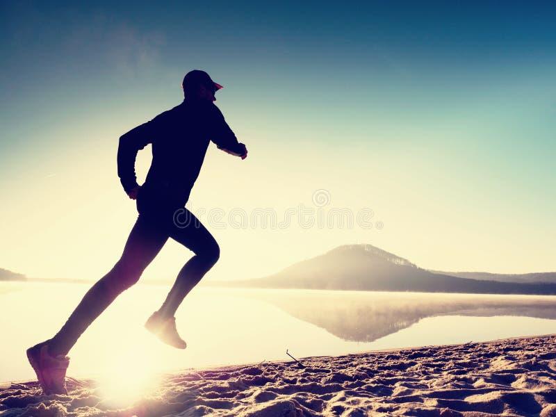 Mann, der auf Strand trainiert Schattenbild des aktiven Mannes trainierend und am See ausdehnend lizenzfreies stockbild