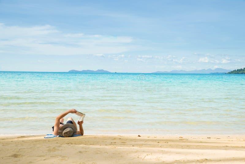 Mann, der auf Strand und Lesebuch stillsteht stockbild
