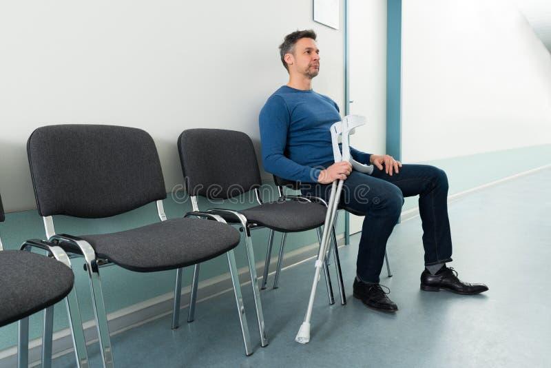 Mann, der auf Stuhl mit Krücken sitzt lizenzfreies stockfoto