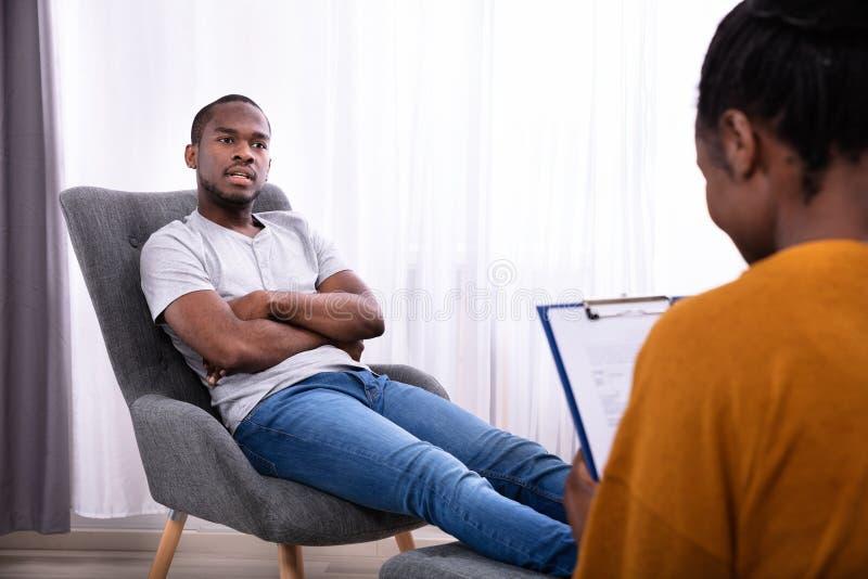 Mann, der auf Stuhl nahe Psychologen sitzt lizenzfreie stockfotografie