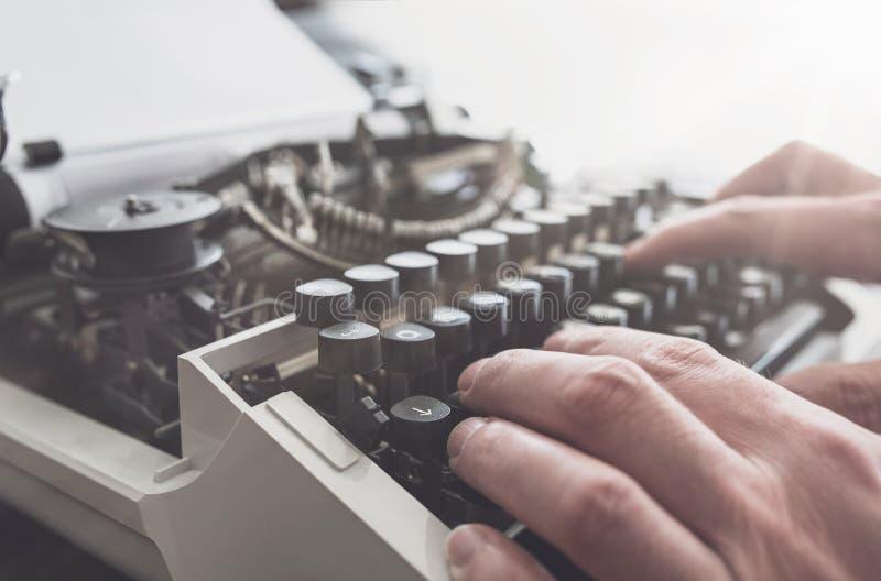 Mann, der auf Tastatur der alten manuellen Schreibmaschine schreibt lizenzfreie stockfotos
