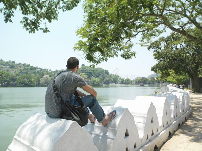 Mann, der auf Umfassungswand durch Fluss sitzt stockfoto