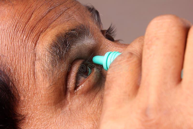 Mann, der Augentropfen anwendet lizenzfreie stockfotografie