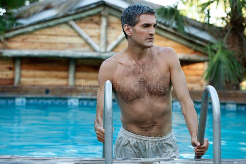 Mann, der aus den Swimmingpool herauskommt stockfotos