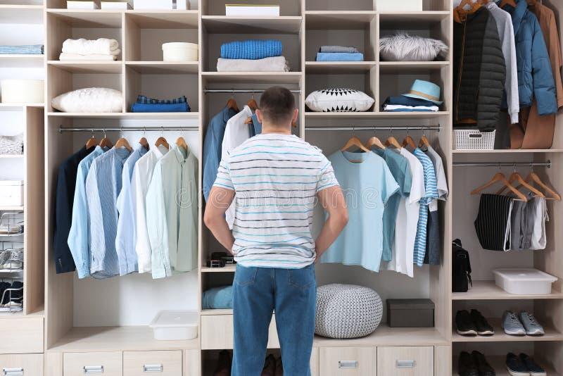 Mann, der Ausstattung vom großen Garderobenwandschrank mit Kleidung, Schuhen und Hauptmaterial wählt lizenzfreie stockfotografie