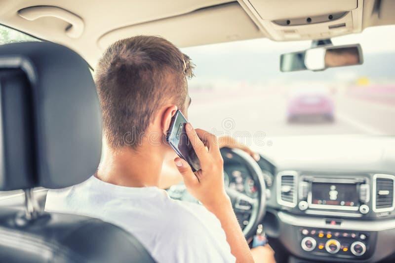Mann, der Auto fährt und vom Smartphone nennt lizenzfreie stockfotos