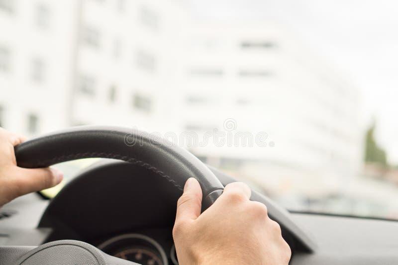 Mann, der Auto in der Stadt fährt Fahrer, der Lenkrad hält stockfotografie