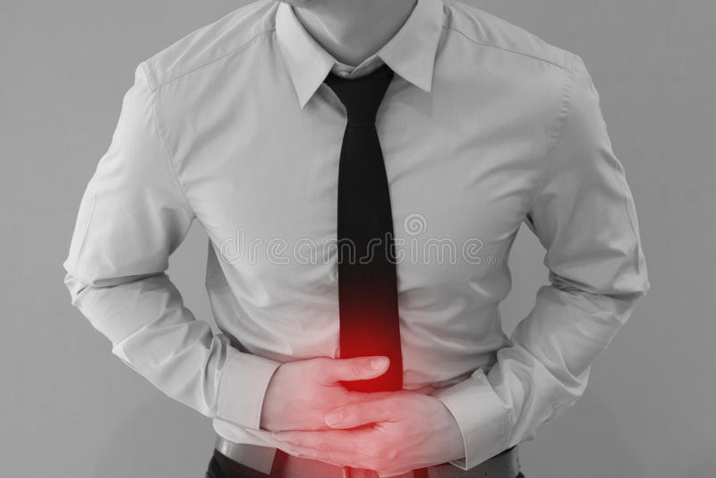 Mann in der Bürouniform, die Magenschmerzen/Lebensmittelvergiftungs-/Magenprobleme hat lizenzfreies stockbild