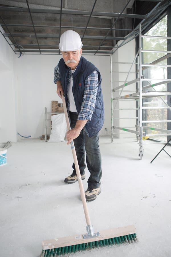 Mann, der Bürste auf Zementboden-Baustelle verwendet lizenzfreie stockfotos