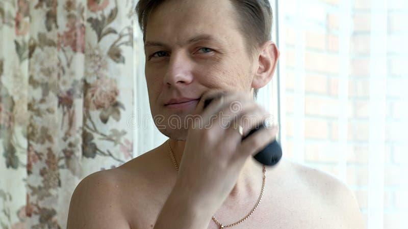 Mann, der Bart mit elektrischem Rasierapparat rasiert Überprüfen Sie das Rasieren, Ihren Finger auf der Backe klauend nahaufnahme lizenzfreie stockbilder