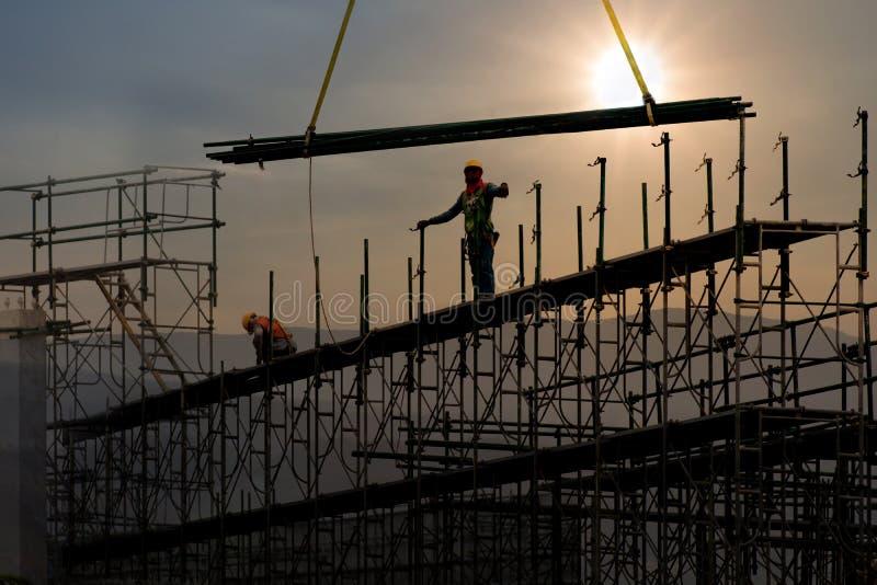 Mann, der an Baustelle mit Gestell arbeitet und mit Sonnenunterganghintergrund, Baugerüst für Baufabrik errichtet lizenzfreies stockbild