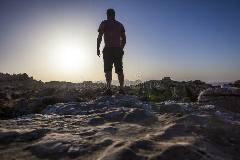 Mann, der bei Sonnenaufgang über felsigem Boden anstarrt Torcal-Naturpark lizenzfreies stockbild