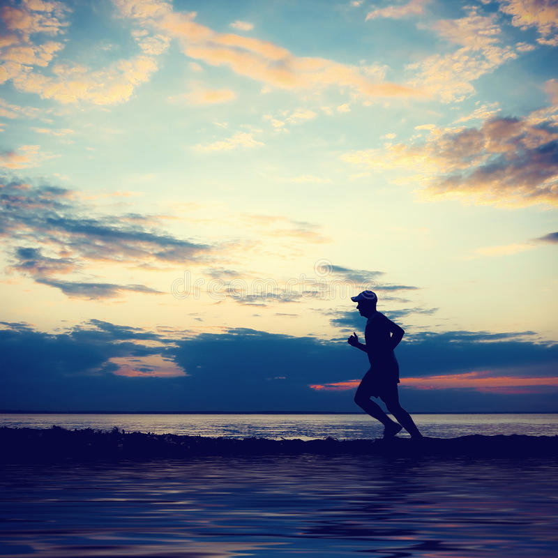 Mann, der bei Sonnenuntergang läuft stockfotos