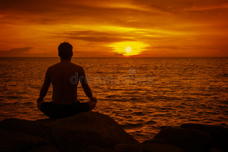 Mann, der bei Sonnenuntergang meditiert. Tropischer Strand von Thaila lizenzfreie stockbilder