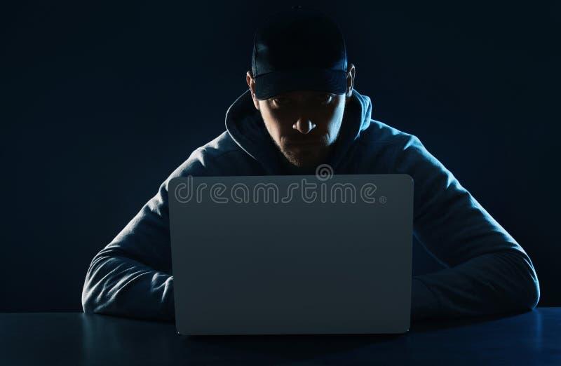 Mann, der bei Tisch Laptop verwendet KRIMINELLE AKTIVIT?T lizenzfreies stockfoto