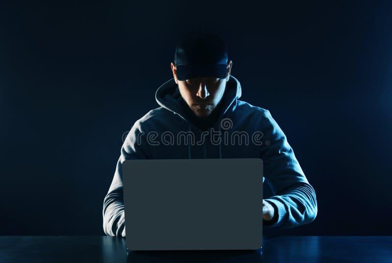 Mann, der bei Tisch Laptop verwendet KRIMINELLE AKTIVIT?T stockfoto