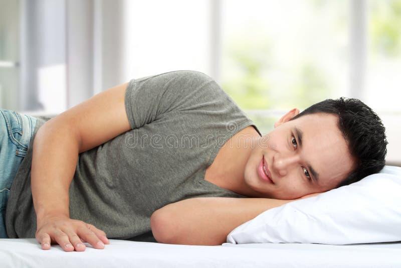 Mann, der beim Bettlächeln liegt stockfotografie