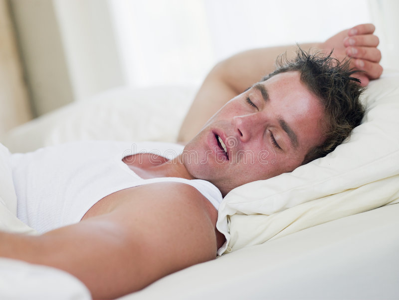 Mann, der beim Bettschlafen liegt lizenzfreie stockfotografie