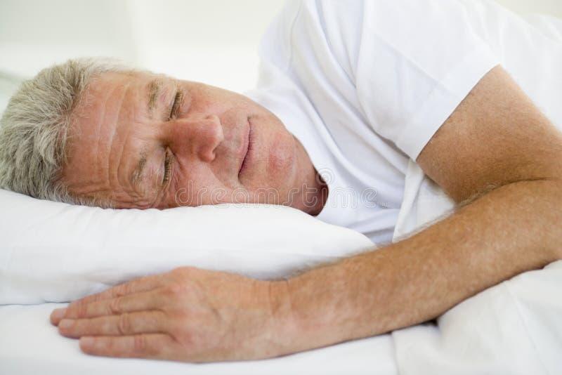 Mann, der beim Bettschlafen liegt stockfotos