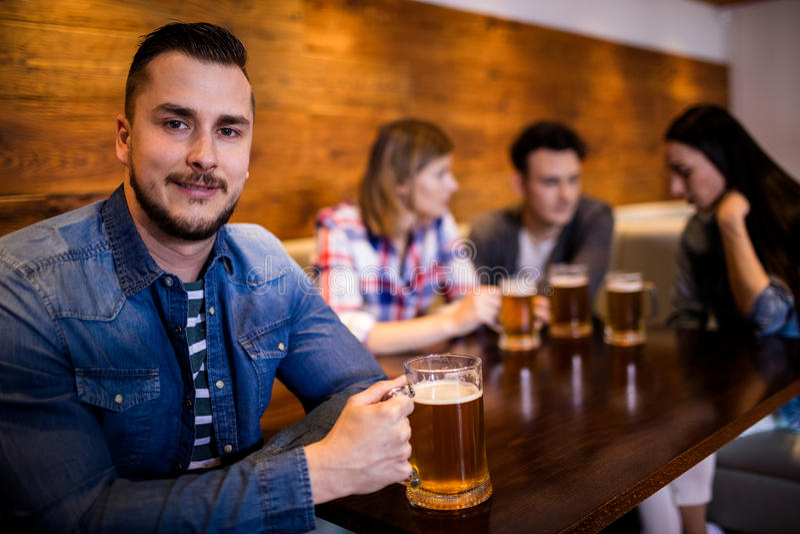 Mann, der Bierkrug während Freunde im Hintergrund hält stockbilder