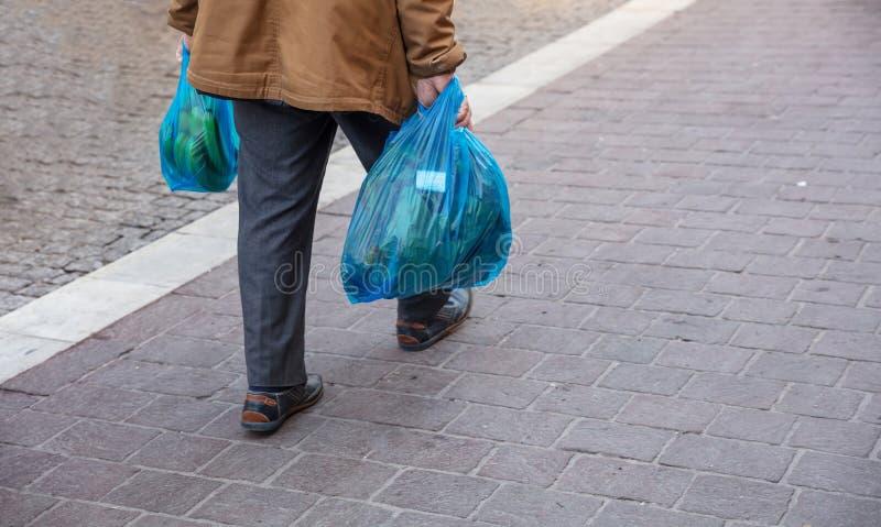Mann, der blaue Plastiktaschen hoding ist Nahaufnahmeansicht, Kopienraum stockbilder