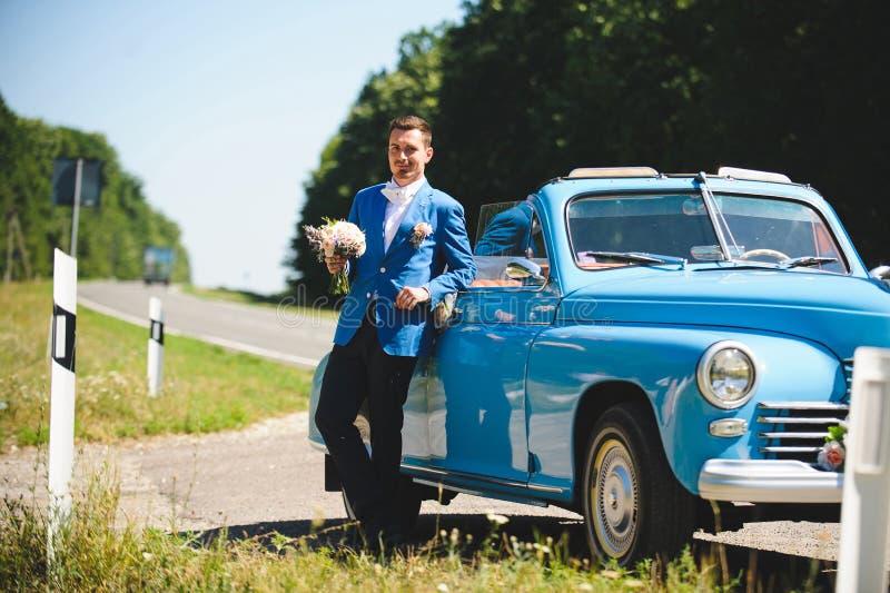 Mann in der blauen Klage am blauen Cabriolet stockfotos
