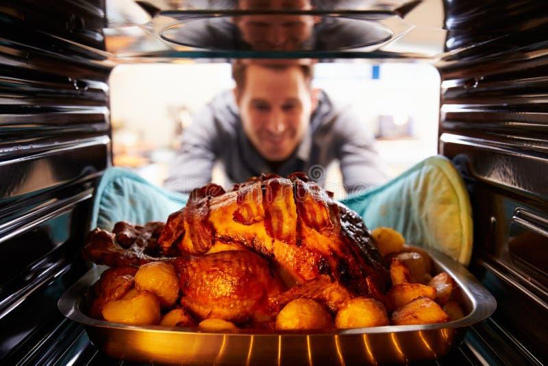 Mann, der Braten die Türkei aus dem Ofen heraus nimmt stockfotos