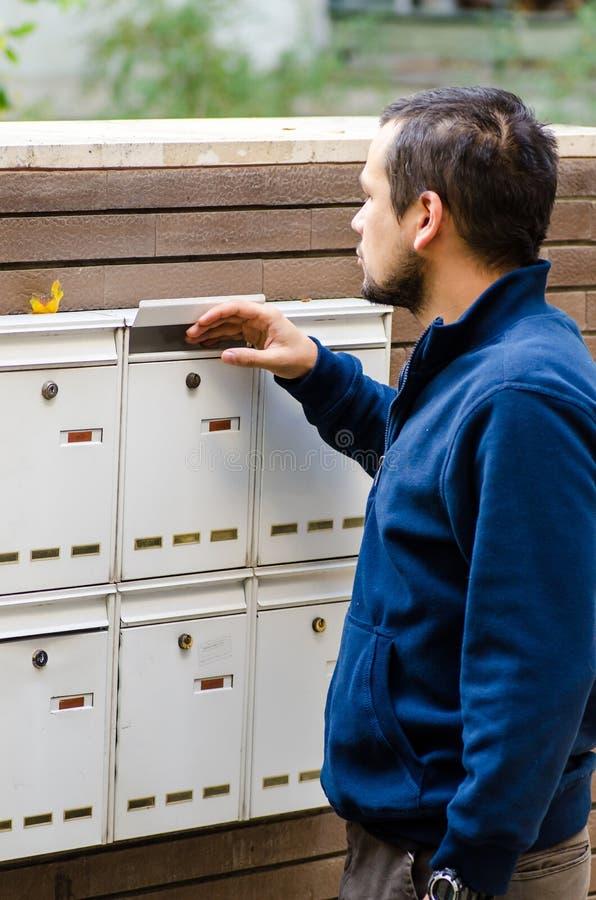 Mann, der Briefkasten überprüft stockbilder