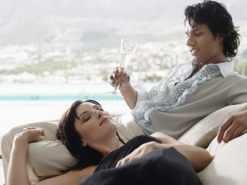 Mann, der Champagne With Woman Lying On seins Schoss trinkt stockbild