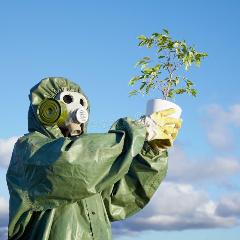 Mann in der chemischen Klage und Gasmaske mit Anlage stockfotografie