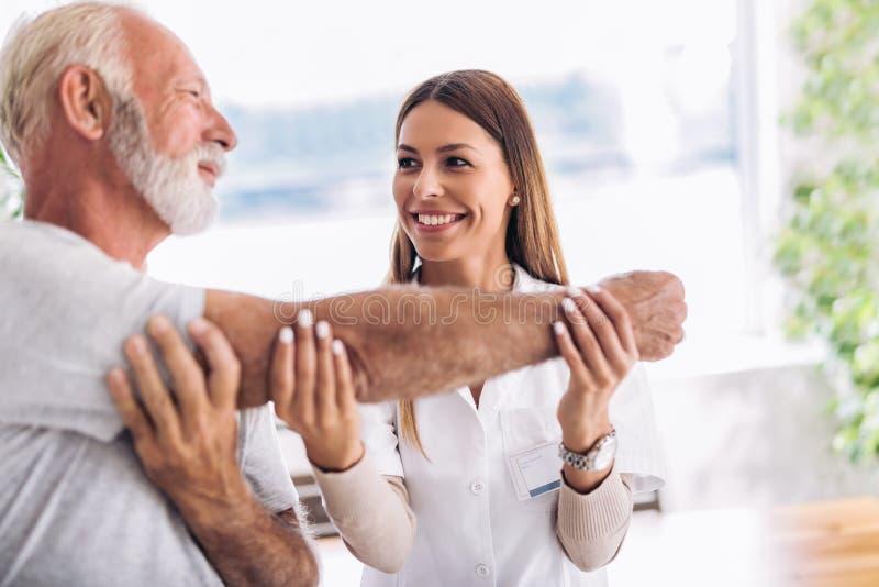 Mann, der Chiropraktikarmanpassung hat lizenzfreie stockfotos